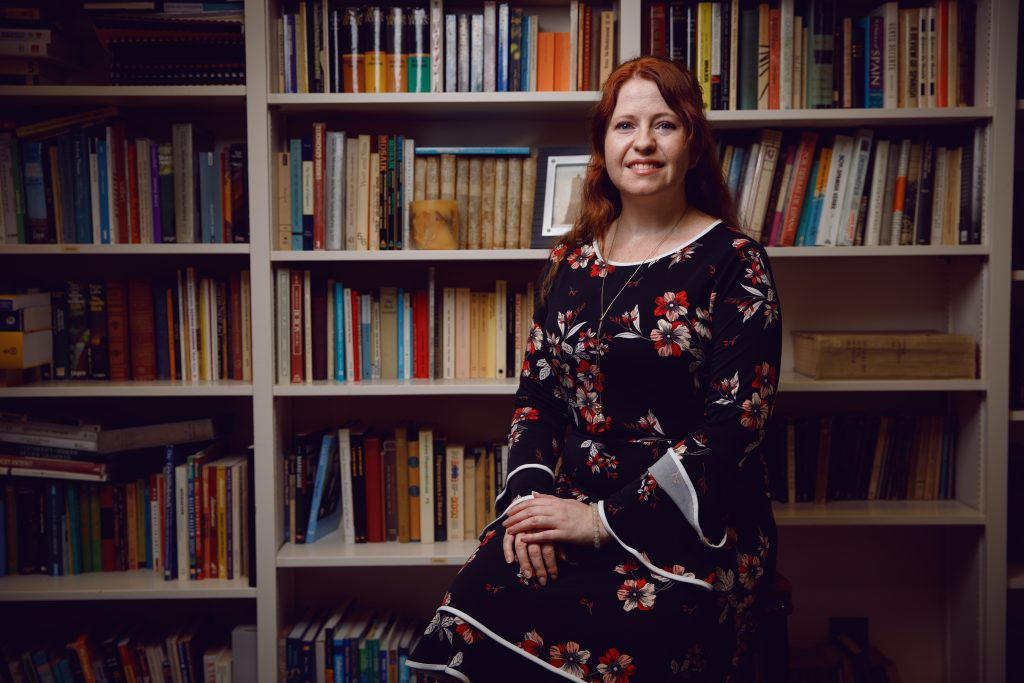 Stacey Jacobson sits in front of a bookcase of colorful Spanish titles in the Department of Modern Languages' library at The University of Alabama.
